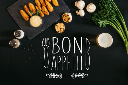 top view of delicious baked potatoes with sauce, spices and glass of beer on black with bon appetit lettering with fork and knife