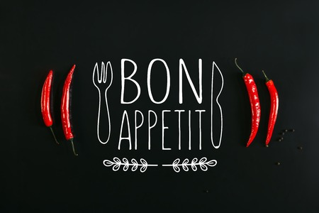top view of red chili peppers and peppercorns on black background with bon appetit lettering with fork and knife