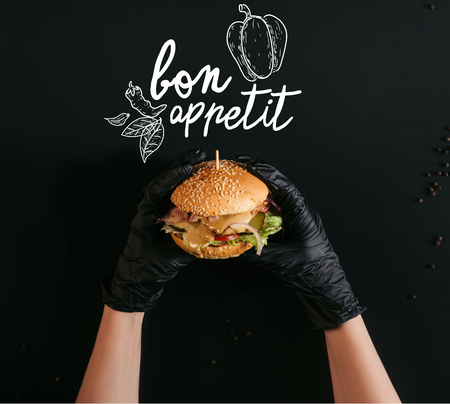 cropped shot of hands in gloves holding delicious burger with turkey, vegetables and caesar dressing on black with bon appetit lettering
