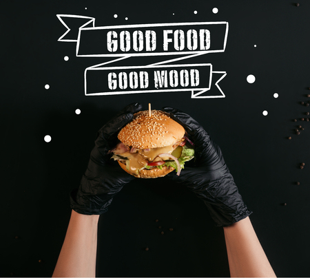 cropped shot of hands in gloves holding delicious burger with turkey, vegetables and caesar dressing on black with good food - good mood inspiration Imagens