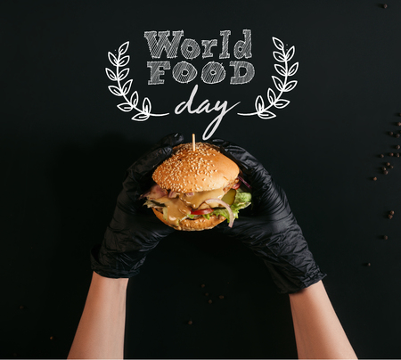cropped shot of hands in gloves holding delicious burger with turkey, vegetables and caesar dressing on black with world food day lettering Imagens