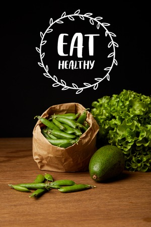 close-up shot of avocado, green peas and lettuce on wooden surface with eat healthy lettering Banco de Imagens