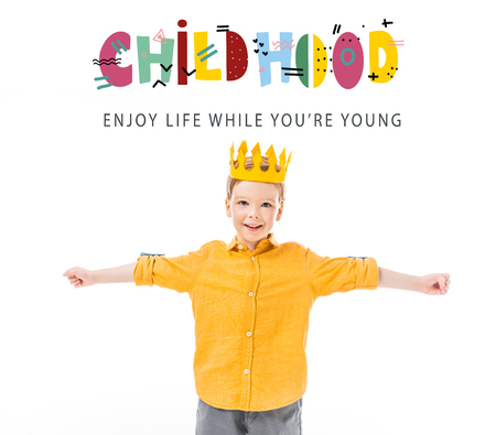 happy boy in yellow crown with outstretched hands isolated on white with childhood - enjoy life while you are young lettering