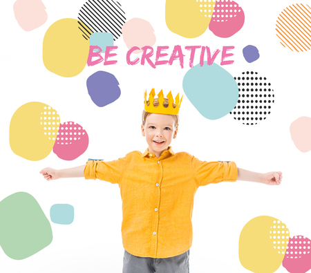 happy boy in yellow crown with outstretched hands isolated on white with be creative inspiration