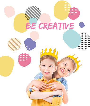 sister hugging brother, kids in yellow paper crowns, isolated on white with
