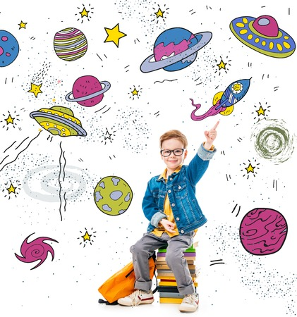 smiling schoolboy pointing up while sitting on pile of books with backpack, isolated on white with fantasy universe, planets and spaceships Stock Photo