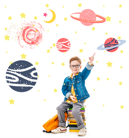 smiling schoolboy pointing up while sitting on pile of books with backpack, isolated on white with fantasy universe and planets
