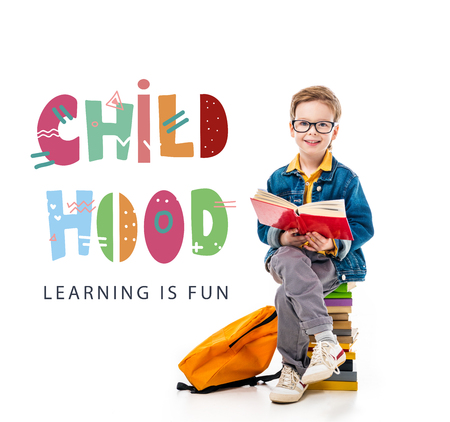 cheerful schoolboy reading book and sitting on pile of books with backpack, isolated on white with childhood - learning is fun lettering Stock Photo
