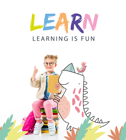 adorable smiling pupil showing thumb up while sitting on pile of books with imaginary dinosaur isolated on white with learn - learning is fun lettering