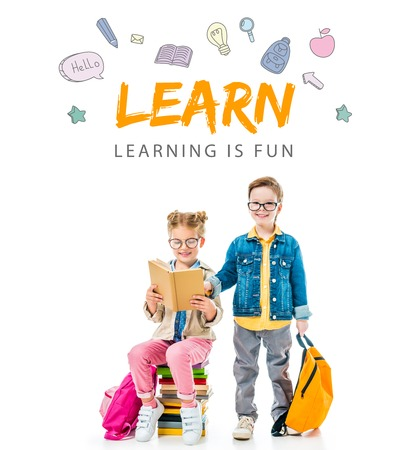 schoolchildren in eyeglasses studying and sitting on books with backpacks, isolated on white with learn - learning is fun lettering Stock Photo
