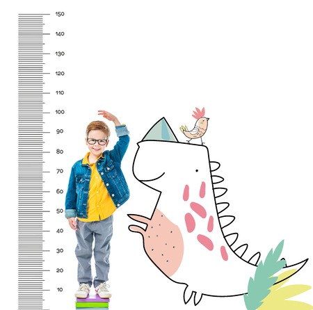 boy standing on pile of books to be higher, isolated on white with imaginary dinosaur and growth measures Stock Photo