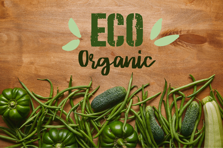 Green beans and organic vegetables on wooden table with eco organic lettering Фото со стока