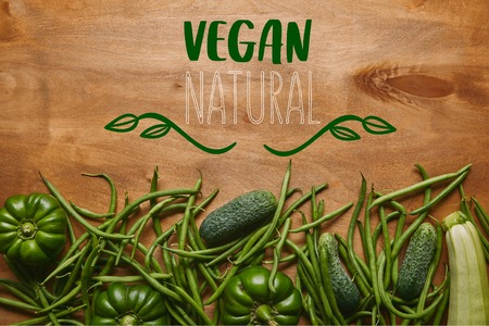 Green beans and organic vegetables on wooden table with