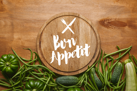 Cutting board with bon appetit lettering with green vegetables on wooden table