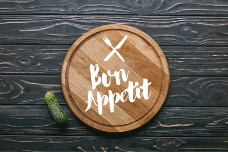 Cutting board with bon appetit lettering and cucumber on dark wooden table