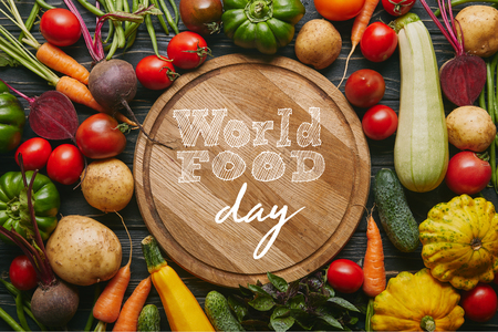 Variety of colorful vegetables by cutting board with world food day lettering