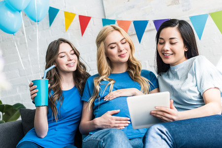 multicultural friends and pregnant woman using tablet at baby shower party Stock Photo
