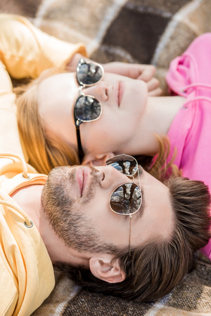 stylish young couple in sunglasses laying on woolen plaid