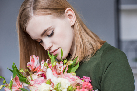 attractive young woman sniffing bouquet of flowers