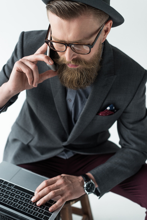 Handsome businessman in vintage style clothes talking on smartphone and working on laptop isolated on light background