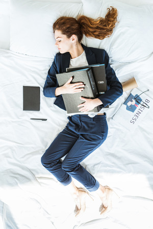 Top view of businesswoman in suit sleeping and holding folders in bed