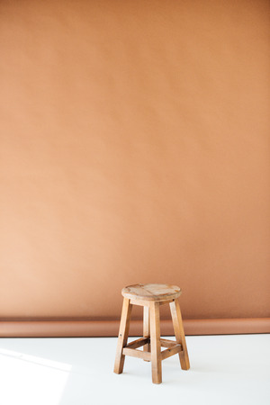 Empty wooden stool on brown background Stok Fotoğraf