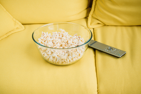 glass bowl with popcorn and remote control on yellow sofa Stockfoto