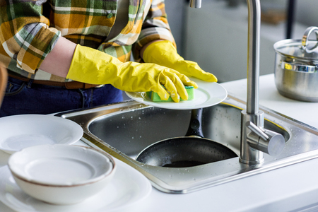 cropped image of woman washing plate in kitchen