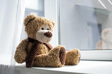 Vue rapprochée de mignon ours en peluche sur le rebord de la fenêtre
