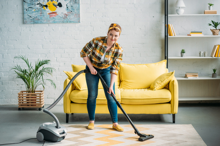 beautiful woman cleaning carpet with vacuum cleaner at home Stock Photo