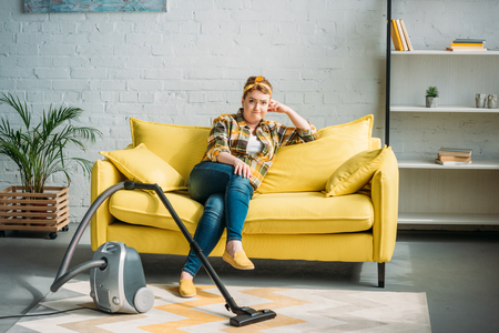 grimacing woman sitting on sofa and looking at camera, vacuum cleaner on floor at home