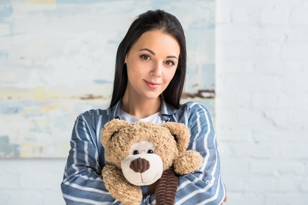 portrait of young attractive woman with teddy bear in hands looking at camera at home