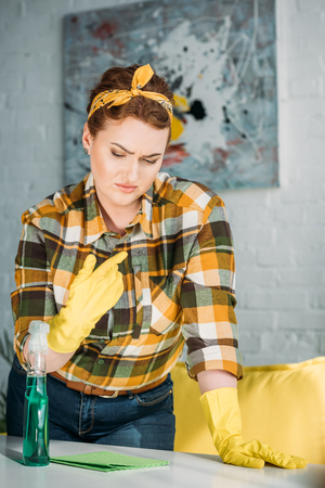 beautiful woman checking dust on table for cleaning at home