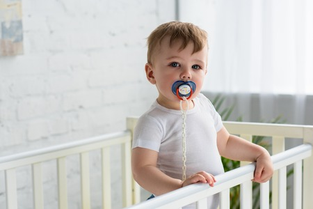 cute little baby boy with pacifier in baby crib looking at camera at home
