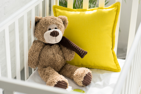 close up view of teddy bear and yellow pillow in baby crib at home Banco de Imagens