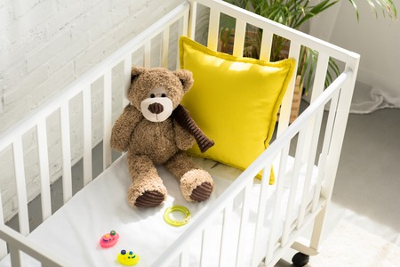 high angle view of teddy bear, other toys and yellow pillow in baby crib at home