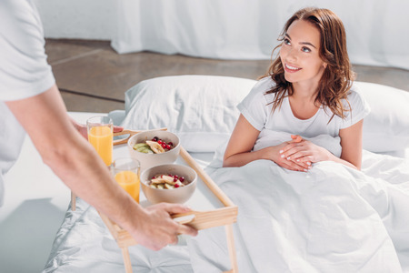 partial view of man brought breakfast in bed for smiling girlfriend Stock Photo