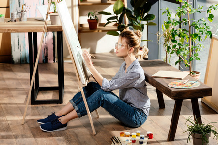 young stylish female artist in eyeglasses painting on easel
