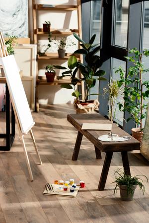 Intérieur de l'atelier d'artiste avec des fournitures de peinture, des plantes en pot et un banc Banque d'images