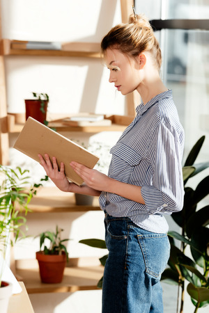 side view of young woman reading book near potted plants