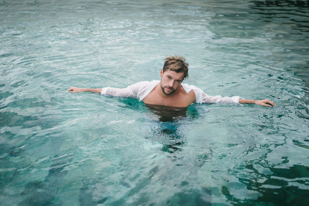 sexy handsome man in swimming pool in Bali, Indonesia Stock Photo