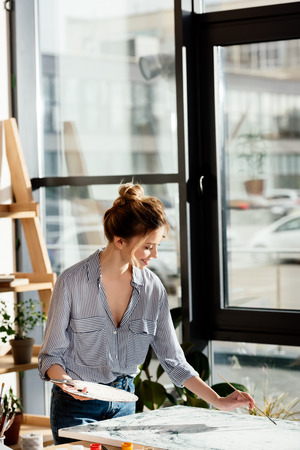 smiling female artist with palette and paintbrush drawing picture in studio Stok Fotoğraf