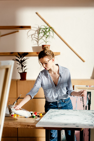 female artist with paintbrush behind ear taking palette at table with painting and paints