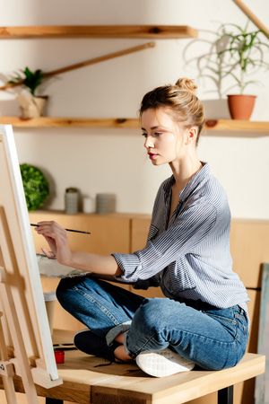 female artist sitting on table and drawing picture by paintbrush Stok Fotoğraf
