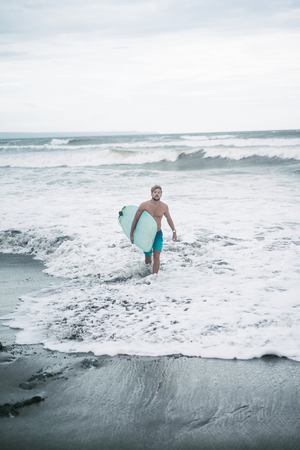 handsome surfer walking from ocean on beach with surfboard in Bali, Indonesia