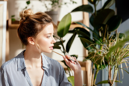 profile of young female artist with paintbrush in hands with potted plants behind