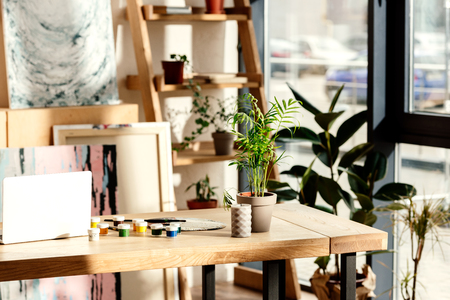 interior of artist studio with painting supplies, laptop and potted plants