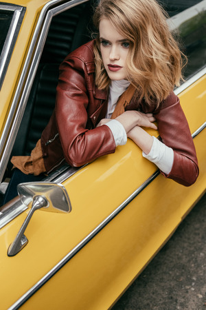 attractive girl in leather jacket looking through window of yellow vintage car