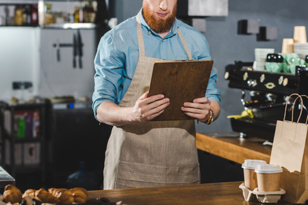 cropped shot of serious young bearded barista holding clipboard in coffee shop Banco de Imagens