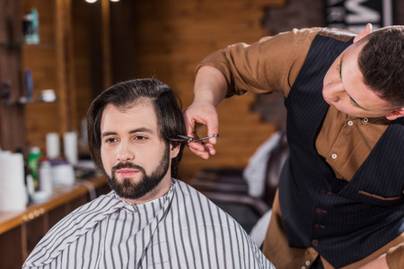 handsome young man getting haircut from professional barber at barbershop Фото со стока - 109417126